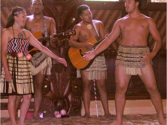 Skirts made of Phormium leaves being worn in performance before tourists in New Zealand.
